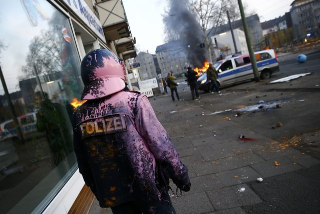 A German police officer who was hit by a paint bomb by anti-capitalist protesters looks at a burning police car near the European Central Bank (ECB) building hours before the official opening of its new headquarters in Frankfurt March 18, 2015. (Photo by Kai Pfaffenbach/Reuters)