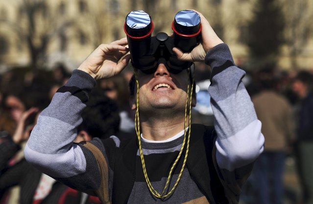 A man watches the partial solar eclipse with binoculars in Zagreb March 20, 2015. (Photo by Antonio Bronic/Reuters)
