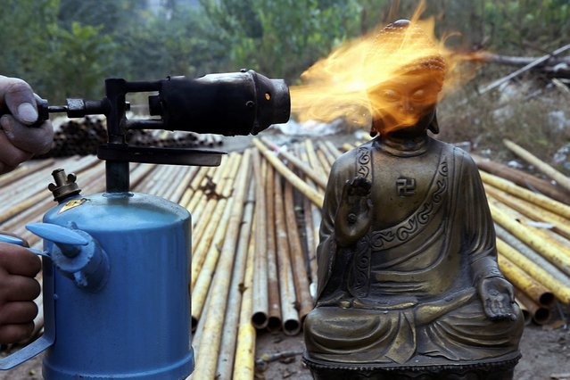 A worker burns off wax covering a Buddha statuette before regilding it during the renovation of Guangren Temple in Xi'an, Shaanxi province, China, on November 5, 2013. (Photo by Rooney Chen/Reuters)