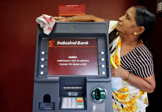 A woman cleans an ATM which is out of service in Mumbai, India, November 11, 2016. (Photo by Danish Siddiqui/Reuters)