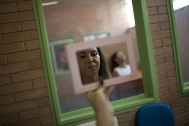 An inmate looks into a mirror as she prepares to compete in the 13th annual Miss Talavera Bruce beauty pageant at the penitentiary the pageant is named for, in Rio de Janeiro, Brazil, Tuesday, December 4, 2018. The event aims to improve the women's self-esteem and is an opportunity to unite with family members they seldom see. (Photo by Silvia Izquierdo/AP Photo)