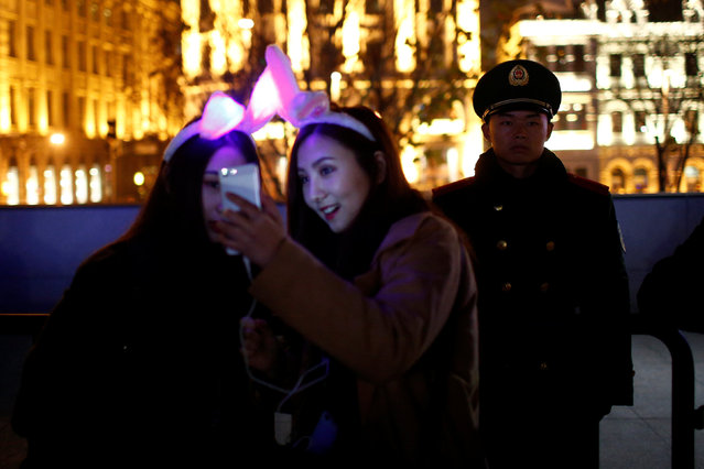 Women take a selfie next to a police officer as they take part in New Year's Eve celebrations in the Bund, in Shanghai, China December 31, 2016. (Photo by Aly Song/Reuters)
