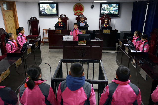 Primary school students take part in a courtroom trial simulation during a week-long publicity campaign for China's Constitution Day in Aksu Prefecture, Xinjiang Uighur Autonomous Region, China on December 4, 2018. (Photo by Reuters/China Stringer Network)