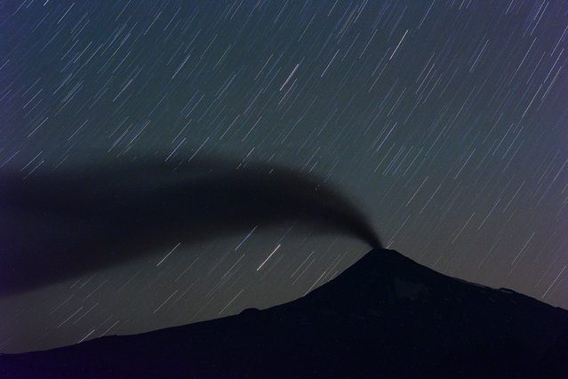 A long exposure picture shows a general view of Villarrica volcano seen at night from Pucon, Cautin Province, some 780 km south of Santiago de Chile, Chile, 22 March 2015. Authorities mantain the orange alert level after the increasing of the activity of the volcano, which could generate an eruption. (Photo by Felipe Trueba/EPA)