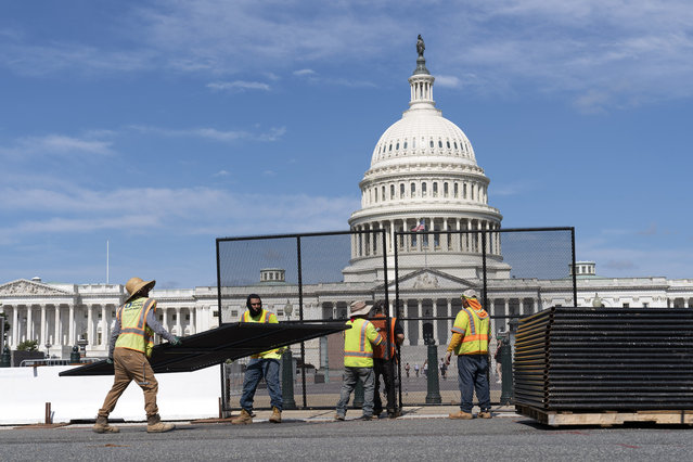 Workers remove the fence surrounding the U.S. Capitol building, six months after it was erected following the Jan. 6 riot at the Capitol, on Saturday, July 10, 2021, in Washington. (Photo by Jose Luis Magana/AP Photo)