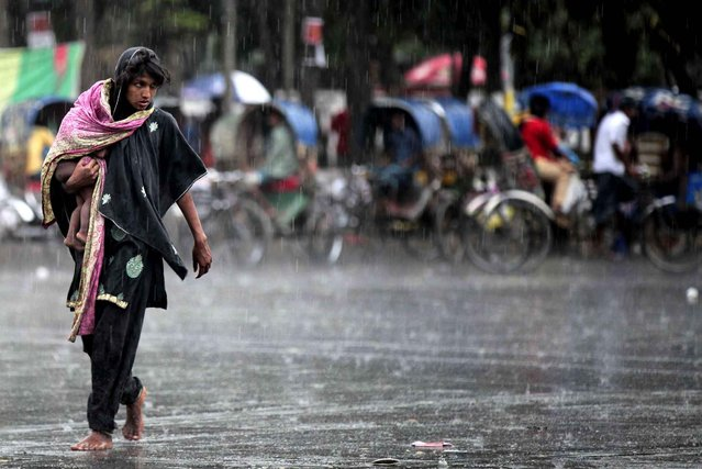 An impoverished Bangladeshi woman carries a child and crosses a road in the rain in Dhaka, Bangladesh, Wednesday, March 18, 2015. A 2013 World Bank report said there was a continuous decline in the number of poor people in Bangladesh, one of the most densely populated countries in the world, from nearly 63 million in 2000, to 55 million in 2005, and then 47 million in 2010. (Photo by A. M. Ahad/AP Photo)