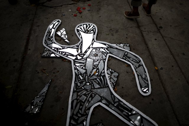 A protester pauses by a glass memorial on the spot where Charly Leundeu Keunang, 43, was shot by police on skid row, during a march to commemorate the more than 617 people they say have been killed by law enforcement in LA County since 2000, in Los Angeles, California April 7, 2015. (Photo by Lucy Nicholson/Reuters)