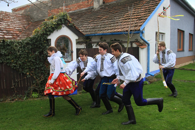 Boys in traditional dresses symbolically beat a girl (L) with small whips during a traditional Easter festivity on Easter Monday, April 6, 2015, in the village of Vlcnov in the southeastern region of the Czech Republic. The whipping of girls on Easter Monday is a tradition that is not intended to cause suffering and a part of the UNESCO Cultural Heritage named Ride of the Kings. (Photo by Radek Mica/AFP Photo)