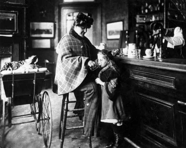 A mother gives her daughter a drink at the bar of a public house, while the baby sleeps in a pram beside her, circa 1900. (Photo by Fox Photos/Getty Images)