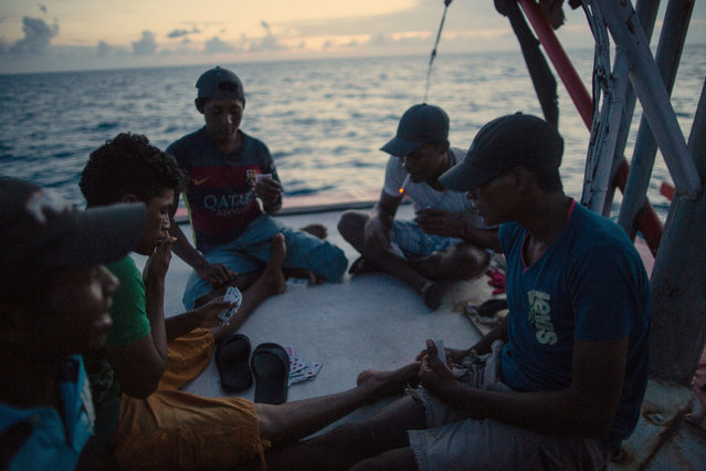 In this September 10, 2018 photo, Miskito divers play a game of cards on a ship's stern as they are transported home after a two week fishing trip, near Savannah Cay, Honduras. (Photo by Rodrigo Abd/AP Photo)
