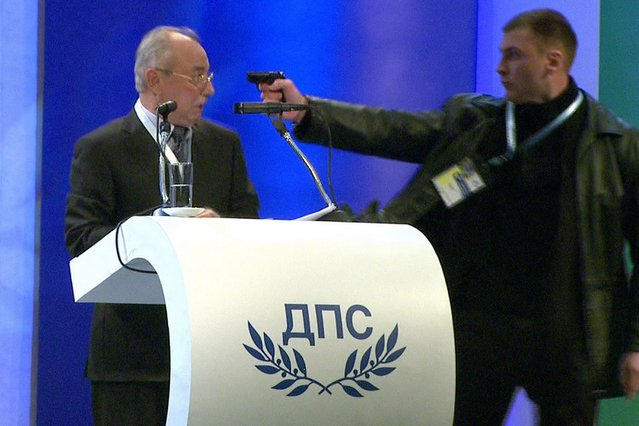 This video grab broadcast by Bulgarian television channel BTV shows a man (R) pointing a pistol at leader of the Turkish minority Movement for Rights and Freedoms (MRF) party Ahmed Dogan during his speech at a national party conference in Sofia on January 19, 2013. (Photo by AFP Photo/BTV)