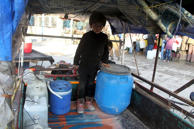A boy stands near water containers after filling them in Bab Neirab, Aleppo, Syria February 15, 2016. (Photo by Abdalrhman Ismail/Reuters)
