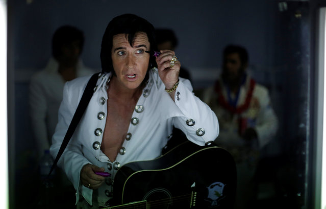 Elvis Presley tribute artist Stephen Fletcher puts on eye make-up in the mirror before competing in a singing contest at the 25th annual Parkes Elvis Festival in the rural Australian town of Parkes, west of Sydney, Australia January 13, 2017. (Photo by Jason Reed/Reuters)