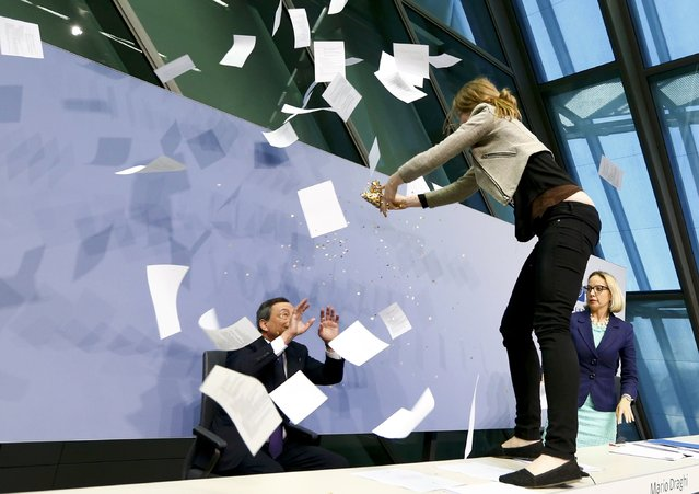 A protester jumps on the table in front of the European Central Bank President Mario Draghi during a news conference in Frankfurt, April 15, 2015. (Photo by Ralph Orlowski/Reuters)