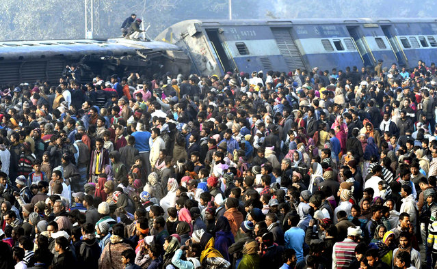 Rescue workers look for survivors as locals stand around the derailed coaches of a train, 30 kilometers (20 miles) north of Patna, the Bihar state capital of India, Sunday, February 3, 2019. Seven coaches of a New Delhi-bound train derailed early Sunday in eastern India, an official said. The cause of the accident is being investigated. (Photo by AP Photo/Stringer)
