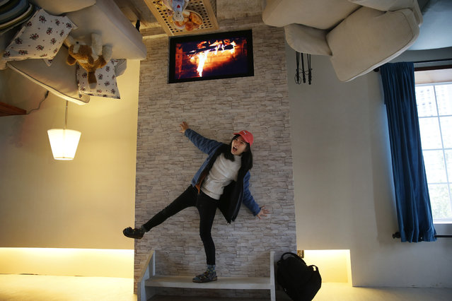 A visitor poses inside an upside-down house created by a group of Taiwanese architects at the Huashan Creative  Park in Taipei, Taiwan, Tuesday, February 23, 2016. (Photo by Wally Santana/AP Photo)