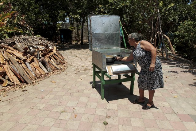 Carmen Selva, who is a member of the Solar Project Foundation for Nicaraguan Women (FUPROSOMUNIC), prepares food in a solar cooker at Diriomo town April 15, 2015. (Photo by Oswaldo Rivas/Reuters)