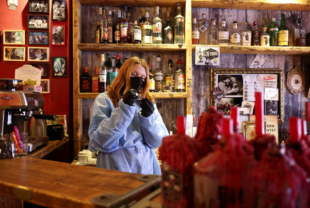 """An employee performs a rapid antigen test at a newly opened testing site at the """"Revolte Bar"""", after the bar was closed due to coronavirus disease (COVID-19) restrictions, in Berlin, Germany, April 15, 2021. (Photo by Christian Mang/Reuters)"""