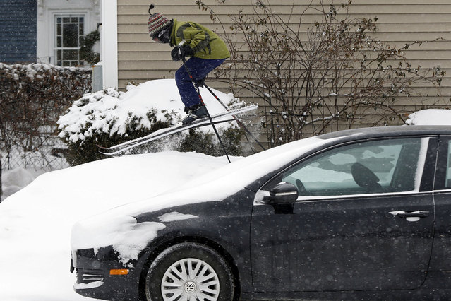 Milo Bloom, 10, skis over a snowbank next to a parked car during a snowstorm, Thursday, January 2, 2014, in Portland, Maine. Strong winds are creating blizzard-like conditions. A wind chill factor of 30 degrees below zero is expected Friday. (Photo by Robert F. Bukaty/AP Photo)