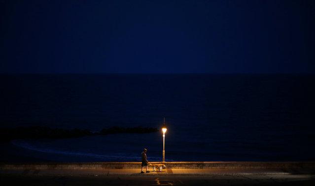 A man walks his dog on the coast of Mar del Plata, Argentina, December 23, 2016. (Photo by Marcos Brindicci/Reuters)