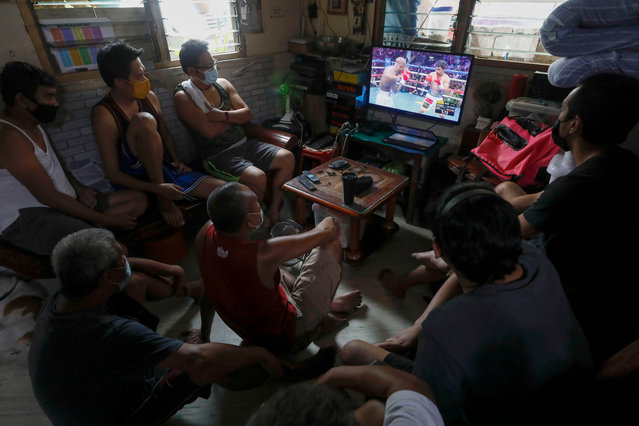 Filipino supporters watch a broadcast of the WBA World Welterweight Championship boxing match between Manny Pacquiao of the Philippines and Yordenis Ugas of Cuba held in the USA, inside a household in Quezon City, Metro Manila, Philippines, 22 August 2021. Filipino fans in the Philippine capital of Metro Manila, who have been known to flock to large public viewing sites to watch Pacquiao's past international boxing matches, had to settle for watching the latest fight in small groups indoors due to COVID-19 quarantine protocols prohibiting mass public gatherings. (Photo by Rolex Dela Pena/EPA/EFE)