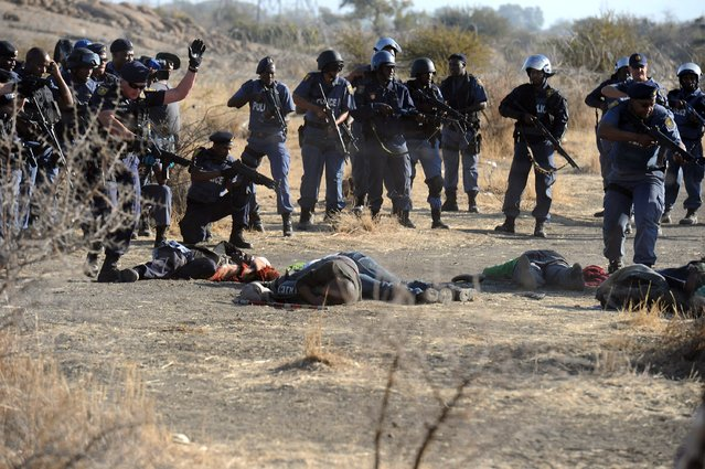 Police surround fallen miners after they opened fire during clashes near a platinum mine in Marikana on August 16, 2012. (Photo by AFP Photo)