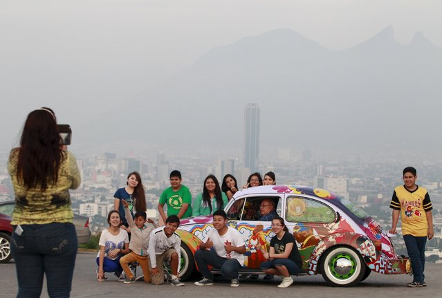 """Rene Penia sits in his VW Beetle 1995, locally called """"Vocho"""", while posing for a photograph with others in Monterrey April 22, 2015. (Photo by Daniel Becerril/Reuters)"""