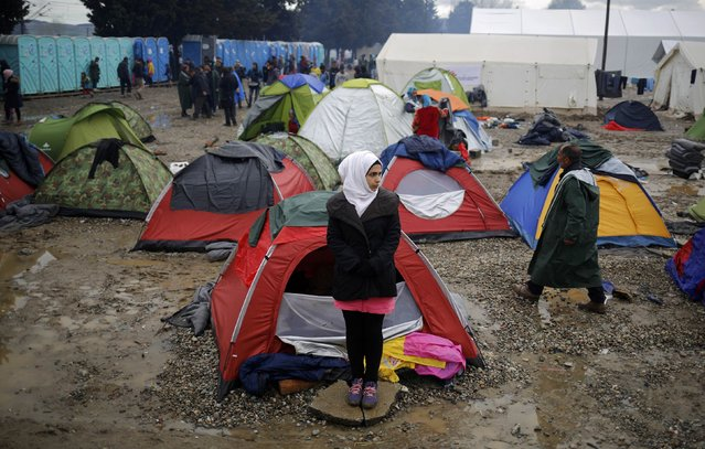 A migrant woman stands outside a tent at a makeshift camp on the Greek-Macedonian border near the village of Idomeni, Greece March 10, 2016. (Photo by Stoyan Nenov/Reuters)