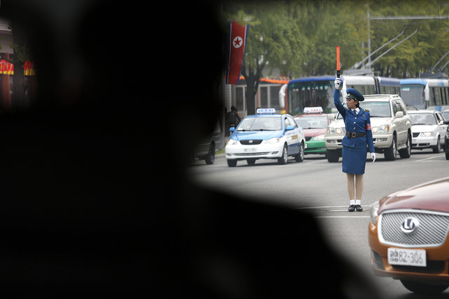 In this October 8, 2015, photo, a North Korean traffic police officer directs vehicles during lunch hour in Pyongyang, North Korea. The streets of Pyongyang are more crowded than ever, but Pyonghwa Motors, North Korea's only passenger car company, whose sole factory was designed to produce as many as 10,000 cars a year, appears to be stuck in neutral. (Photo by Wong Maye-E/AP Photo)