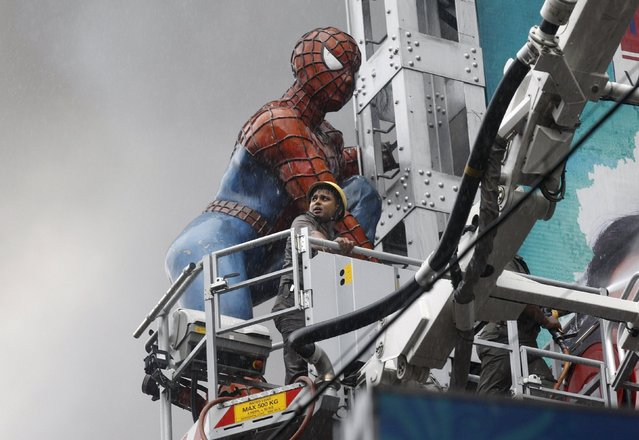A firefighter stands on a ladder next to a Spider-Man statue after a fire broke out in a shopping mall in Kolkata, India, April 26, 2015. (Photo by Rupak De Chowdhuri/Reuters)