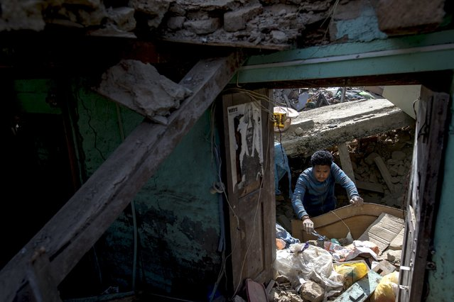 An earthquake survivor searches for belongings in his collapsed house in Sankhu, on the outskirts of Kathmandu, Nepal, May 5, 2015. (Photo by Athit Perawongmetha/Reuters)