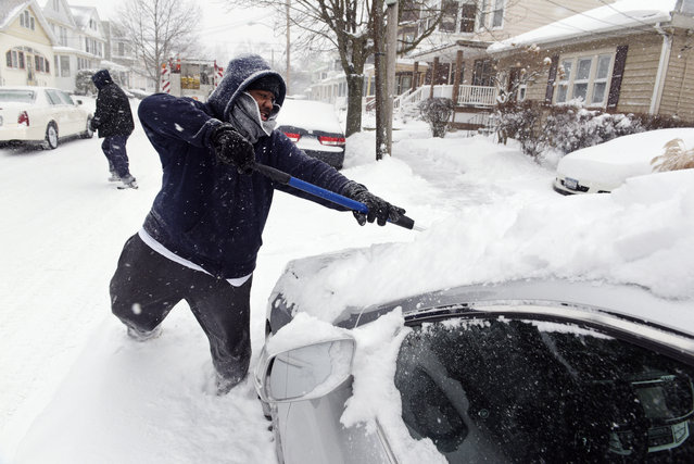 David Springsteen, of Albany, clears the snow off of his girlfriend's grandmother's car as snow falls, Thursday, February 9, 2017, in Albany, N.Y. (Photo by Paul Buckowski/The Albany Times Union via AP Photo)