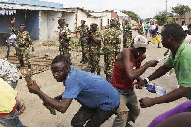 Demonstrators duck and run from soldiers firing into the air to disperse the crowd of demonstrators who had cornered  Jean Claude Niyonzima a suspected member of the ruling party's Imbonerakure youth militia in a sewer in the Cibitoke district of Bujumbura, Burundi, Thursday May 7, 2015. (Photo by Jerome Delay/AP Photo)