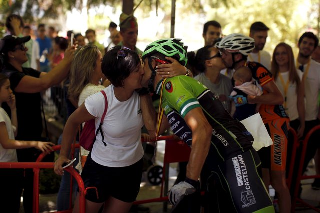 Spanish mountain bikers Jose Antonio Castellanos (L) and Jose Ignacio Rubio (R) kiss their wives after arriving in the second and third place, respectively, in the XVIII 101km international competition in Ronda, southern Spain, May 9, 2015. (Photo by Jon Nazca/Reuters)