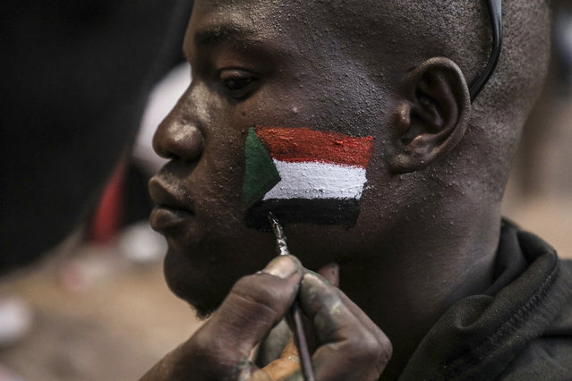 A man's face is painted as Sudanese protesters chant slogans during a rally outside the army headquarters in Sudan's capital Khartoum on Saturday, April 20, 2019.  Sudan's military ousted President Omar al-Bashir following four months of street protests against his rule, then appointed a military council it says will rule for no more than two years while elections are organized. Protesters fear the army, dominated by al-Bashir appointees, will cling to power or select one of its own to succeed him. (Photo by AP Photo)