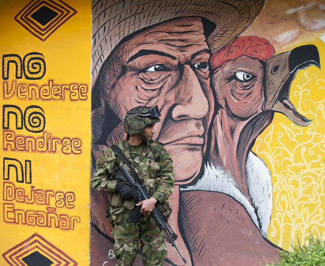 A soldier stands guard outside a polling station in Toribio, deparment of Cauca, during parliamentary elections in Colombia, on March 9, 2014. Colombians went to the polls on Sunday to elect new legislators, in a vote seen as a referendum on peace talks with leftist guerrillas and a bellwether for May's presidential election. (Photo by Luis Robayo/AFP Photo)