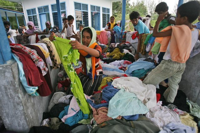 Ethnic Rohingya migrants sift through used clothing donated by local residence at a temporary shelter in Langsa, Aceh province, Indonesia, Saturday, May 16, 2015. (Photo by Binsar Bakkara/AP Photo)