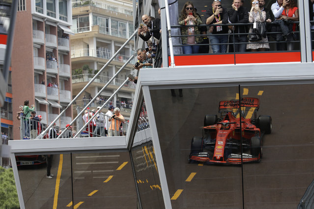 Ferrari driver Sebastian Vettel of Germany is reflected on the glass of the paddock during the second practice session at the Monaco racetrack, in Monaco, Thursday, May 23, 2019. The Formula one race will be held on Sunday. (Photo by Luca Bruno/AP Photo)