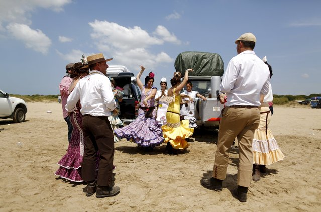 Pilgrims sing and dance on their way to the shrine of El Rocio in Donana National Park, southern Spain May 20, 2015. Every spring hundreds of thousands of devotees converge at a shrine to pay homage to the Virgin del Rocio during an annual pilgrimage which combines religious fervour and festive colour. (Photo by Marcelo del Pozo/Reuters)