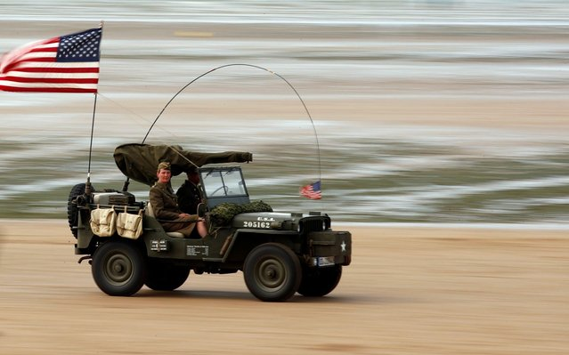Enthusiasts enjoy a ride on a vintage army jeep during a re-enactment of D-Day landings in Arromanches, on the Normandy coast, France on June 3, 2019. (Photo by Christian Hartmann/Reuters)