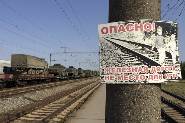 "Multiple launch rocket systems and military trucks are seen on freight train flatcars in the Russian southern town of Matveev Kurgan, near the Russian-Ukrainian border in Rostov region, Russia, May 25, 2015. The sign reads, ""Dangerous! Railway is not a place for games!"". (Photo by Maria Tsvetkova/Reuters)"