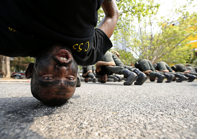 Thai police officers perform patience skill with their heads on the ground during the Commandos Program training at the Crime Suppression Division in Bangkok, Thailand, 26 February 2014. (Photo by Rungroj Yongrit/EPA)