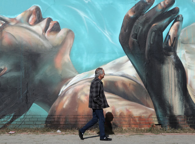 A man walks past an artwork by German artist Norm Abartig (@norm_abartig) and South African artist Nicholas Kerr aka Dekor One (@dekor) as part of the Westdene Graffiti Project in downtown Johannesburg, South Africa, 31 May 2019. The Westdene Graffiti Project has helped raise awareness of the art form of graffiti in the area. The art form has flourished in the inner city as the area has decayed over the past decade. Various artists from both South Africa and the rest of the world have taken their spray cans to the huge walls in South Africa's biggest city. (Photo by Kim Ludbrook/EPA/EFE)