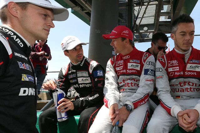 Porsche 919 No18 Swiss driver Neel Jani, second left, has a talk with Audi No7 Swiss driver Marcel Fassler, center, before the start of the 83rd 24-hour Le Mans endurance race, in Le Mans, western France, Saturday, June 13, 2015. (AP Photo/David Vincent)