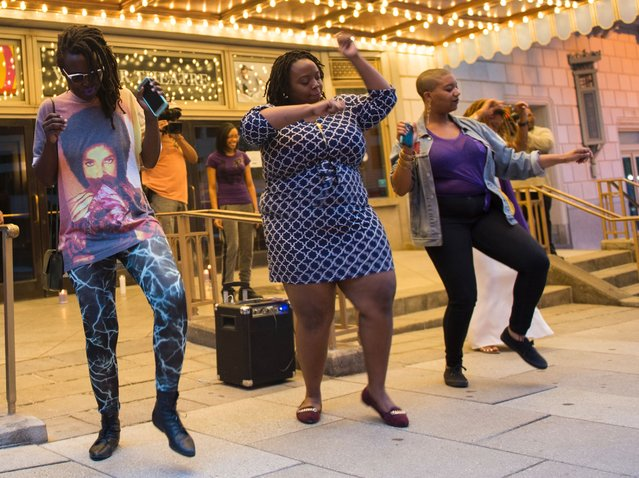 People dance during a candle light vigil in remembrance to Prince outside the Warner Theatre in Washington, DC on April 21, 2016. (Photo by Andrew Caballero-Reynolds/AFP Photo)
