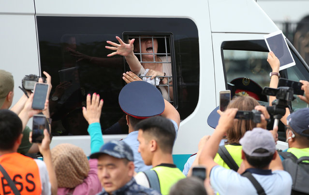 A woman reacts inside a police minibus after she was detained during a protest rally held by Kazakh opposition supporters in Almaty, Kazakhstan on July 6, 2019. (Photo by Pavel Mikheyev/Reuters)