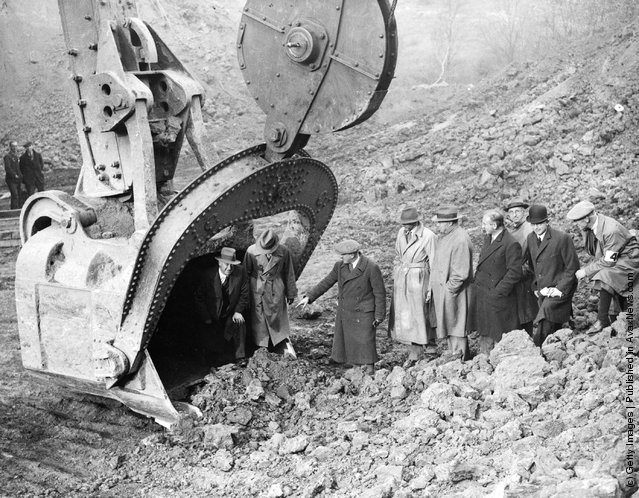 1934: Men emerge from the fifteen ton scoop of Europe's biggest digger at Corby in Northants