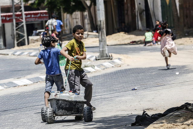 A Palestinian child pulls a cart loaded with jerricans filled with drinking water from public taps in Khan Yunis in the southern Gaza strip on July 10, 2019. The population of Gaza facing a drinking water problem is increasing. Lacking natural resources, the Gaza Strip suffers from a chronic shortage of water, electricity and petrol. More than two-thirds of the population depends on humanitarian aid, which the United Nations says could become uninhabitable by 2020. (Photo by Said Khatib/AFP Photo)