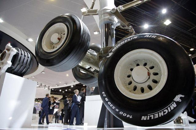 Visitors gather next to the Safran made landing gear of an Airbus A350 aircraft at the Paris Air Show, at Le Bourget airport, north of Paris, Thursday, June 18, 2015. Some 300,000 aviation professionals and spectators are expected at the Paris Air Show, coming from around the world to make business deals and see dramatic displays of aeronautic prowess and the latest air and space technology. (AP Photo/Francois Mori)