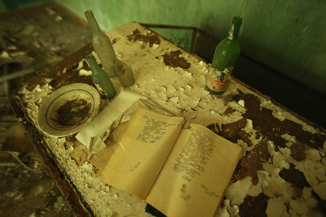A notebook, beer bottles and plate lie on a flaking table in an abandoned house at Zalisya village located inside the Chernobyl Exclusion Zone on September 29, 2015 near Chornobyl, Ukraine. Zalisya, a village that before 1986 had a population of approximately 3,000, lies about 15 kilometers south of the former Chernobyl nuclear power plant, where in 1986 workers inadvertantly caused reactor number four to explode, creating the worst nuclear accident in history. Authorities evacuated 120,000 people, incuding the residents of Zalisya and 85 other villages, as well as of the towns of Chornobyl and Pripyat. (Photo by Sean Gallup/Getty Images)